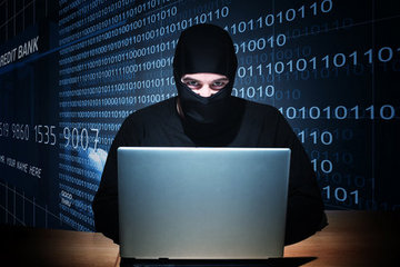 black-hooded, masked man using laptop